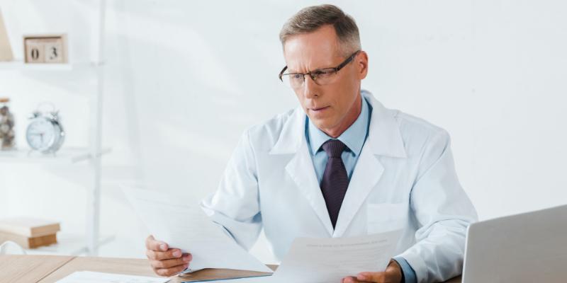perplexed doctor looking at paperwork