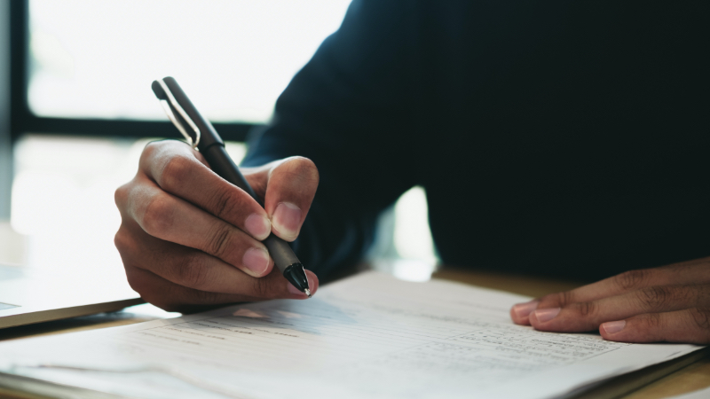 closeup of a hand holding a pen, signing papers