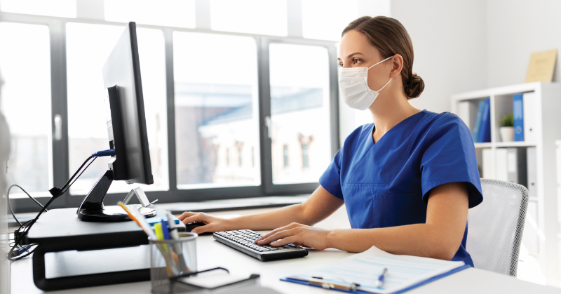 Dental assistant on the computer, wearing a mask.