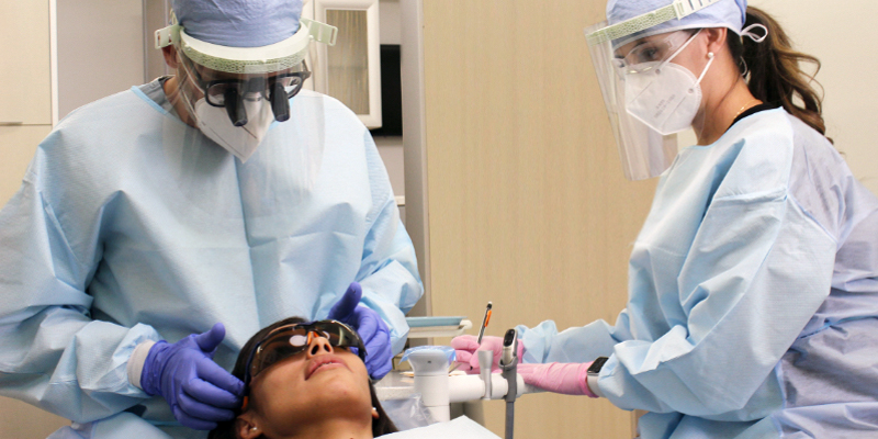 A dentist and assitant, in full PPEs, working on a patient.