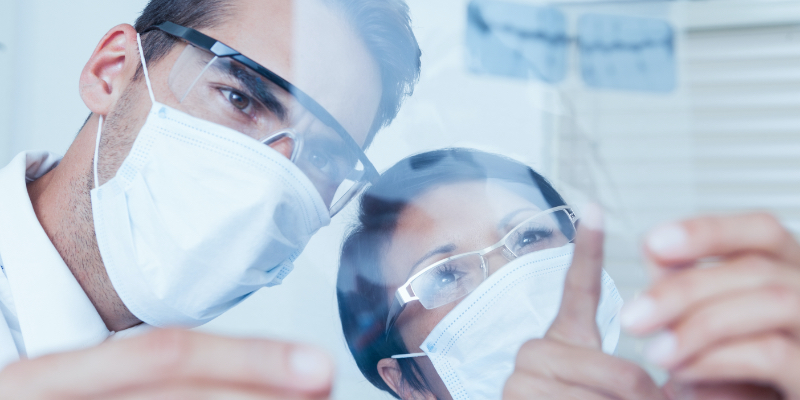 Two dentists with masks and protective eyewear reviewing an xray.