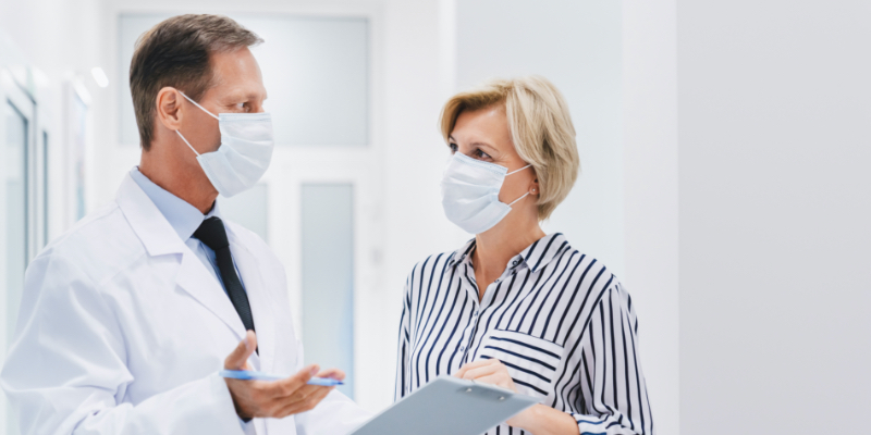 Doctor and Patient having a discussion and wearing PPE