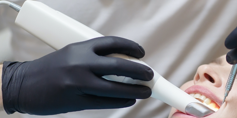 Gloved hands use a wand in a patient mouth.