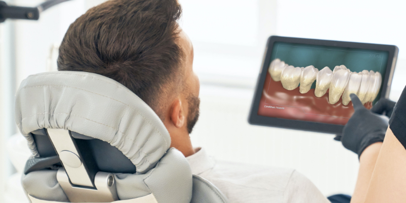Patient reclined in a dental chair views a patient education video on an ipad.