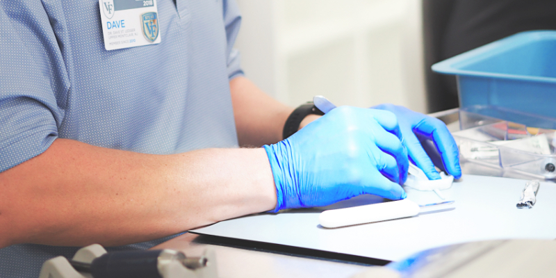 A doctor with rubber gloves writing.